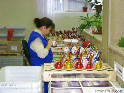 Художник разрисовывает елочную игрушку