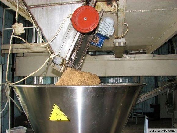 Тесто выползает на конвейер для выпечки хлеба